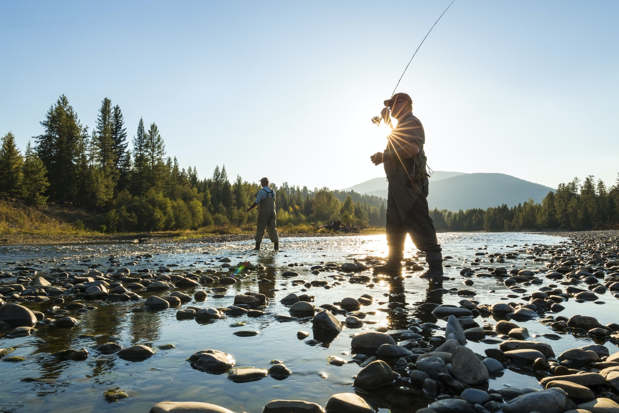 Two fly fisherman standing in rocky riverbed, casting their fishing rods.